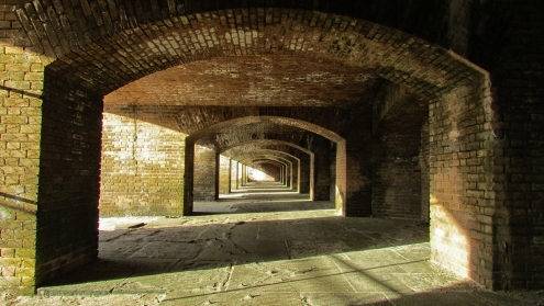 The open casemates of Fort Jefferson's northeastern wall recede into the afternoon sunlight. Each archway delineates a distinct firing position. Had an enemy ship ever approached—and had the fort ever been armed to its full potential—this design would have allowed 125 guns to zero on any given target all at once.